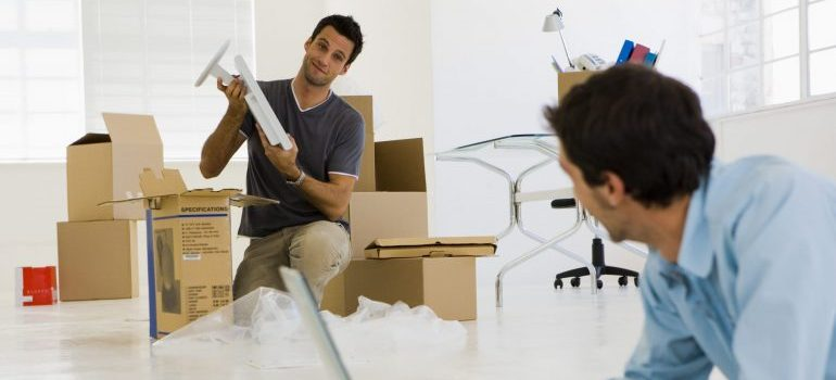 Two guys in an office space with storage boxes.